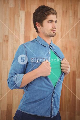 Confident hipster opening shirt in superhero style