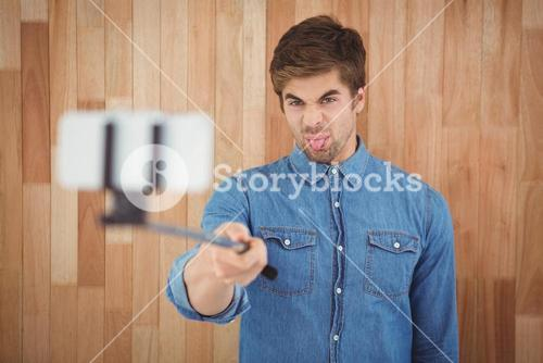 Hipster sticking out tongue while taking selfie
