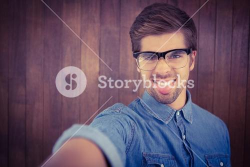 Portrait of hipster sticking out tongue