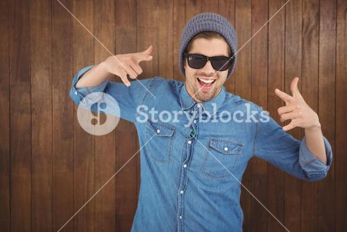 Happy hipster showing rock and roll hand sign