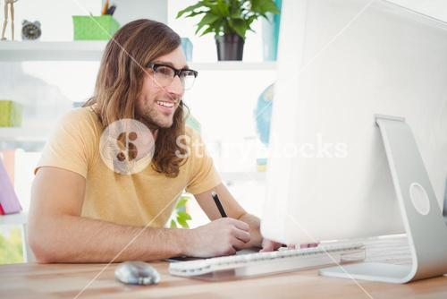 Happy hipster at computer desk