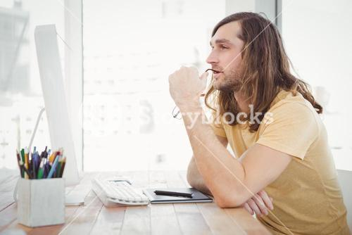 Thoughtful hipster at computer desk