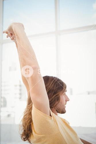 Hipster stretching arms in office