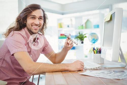 Portrait of happy hipster holding electronic cigarette