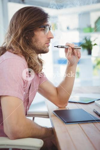 Hipster smoking electronic cigarette at desk in office