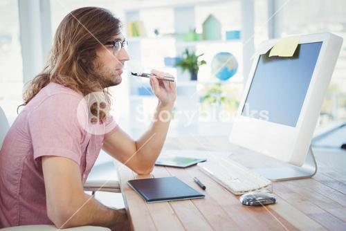 Hipster smoking electronic cigarette at computer desk in office