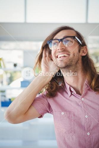 Happy hipster cupping hands to ear