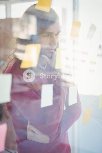 Thoughtful man with hand on chin looking at sticky notes