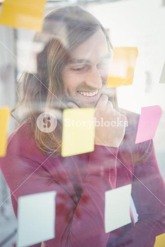 Businessman with hand on chin looking at sticky notes