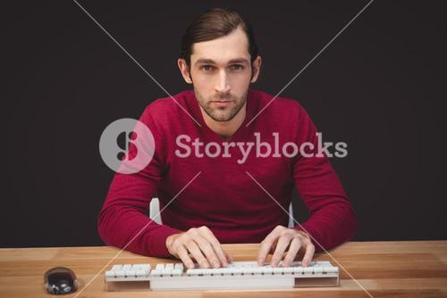 Portrait of serious man typing on keyboard at desk