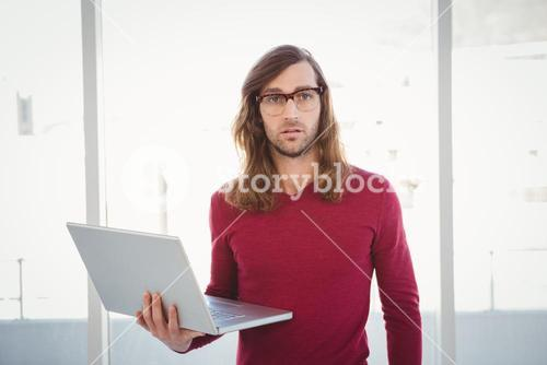 Portrait of hipster holding laptop against window