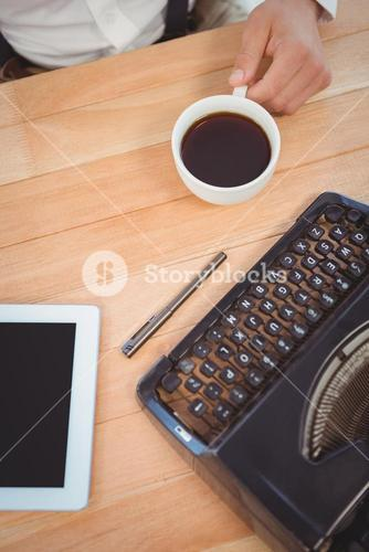 Businessman holding black coffee at desk in office