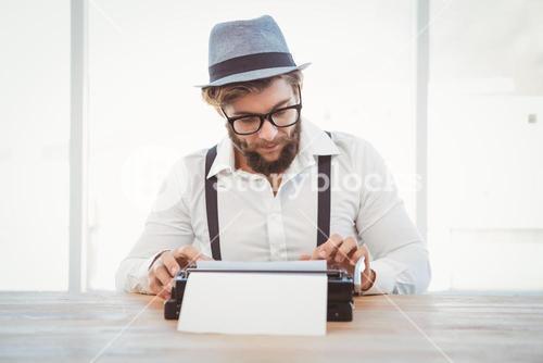 Hipster wearing eye glasses and hat working on typewriter
