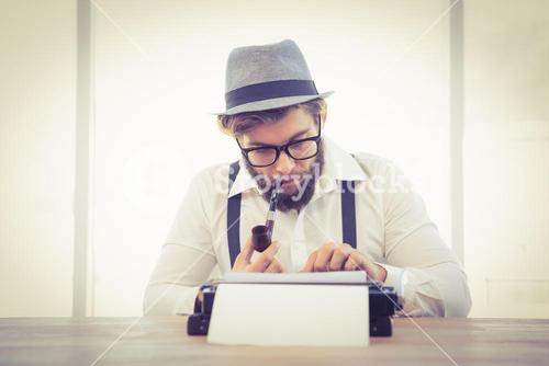 Hipster smoking pipe while working in office