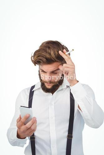 Hipster looking in mobile phonewhile holding cigarette
