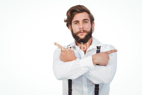 Confident hipster pointing sideways with arms crossed