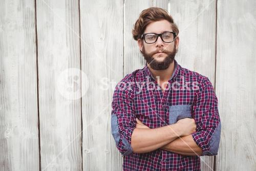 Confident hipster wearing eye glasses with arms crossed