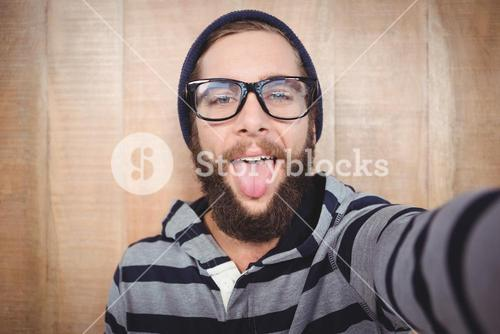 Portrait of happy hipster sticking out tongue