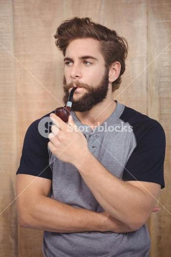 Confident hipster smoking pipe