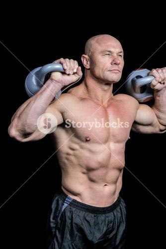Bodybuilder lifting kettlebells