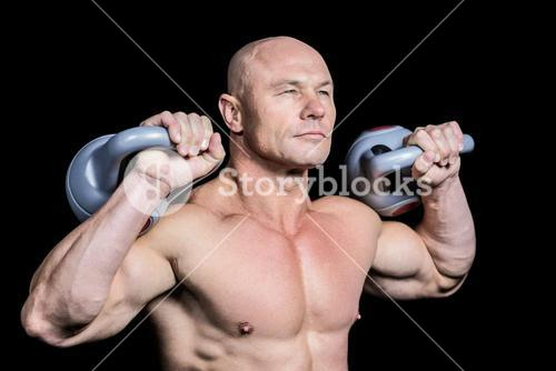 Muscular fit man holding dumbbells