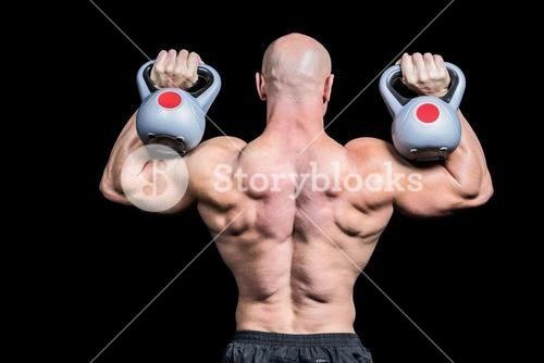 Rear view of bald man lifting kettlebells