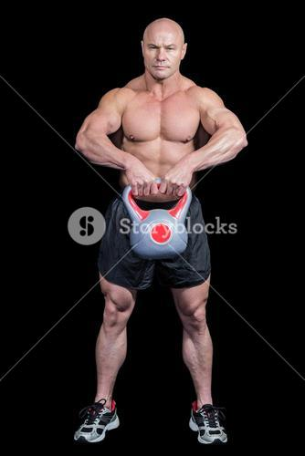 Portrait of bald man lifting kettlebell