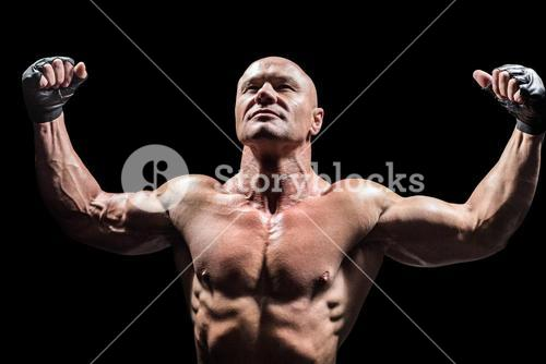 Muscular fighter with arms raised