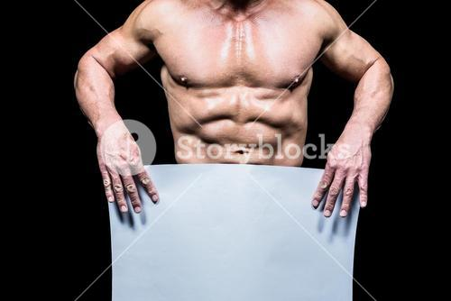 Midsection of muscular man holding white blank paper