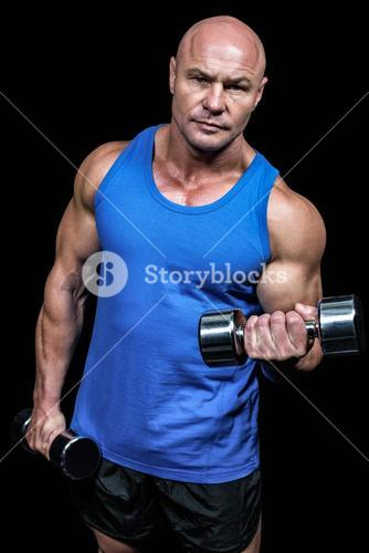 Portrait of man lifting dumbbells