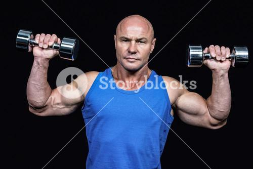 Portrait of man lifting dumbbells with arms raised