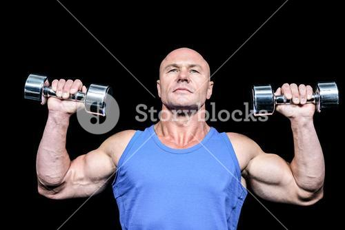Muscular man in vest lifting dumbells