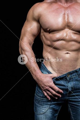 Midsection of sexy man pulling denim