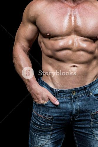 Midsection of shirtless man with hands in pocket