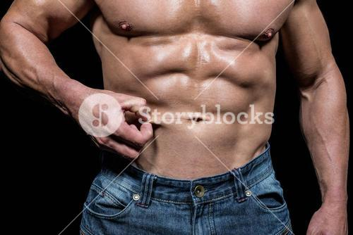 Midsection of muscular man holding skin