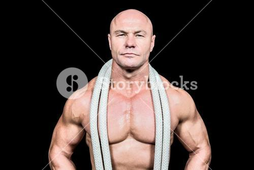 Portrait of confident fit man with rope around neck