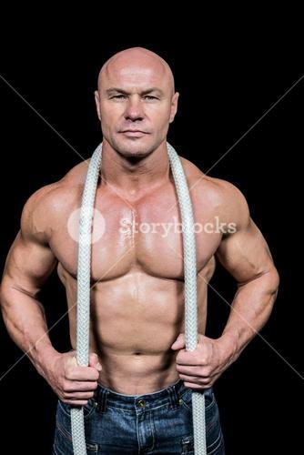 Portrait of healthy man holding rope