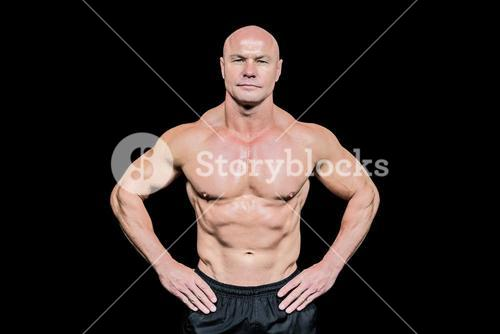 Portrait of confident bald man with hands on hip