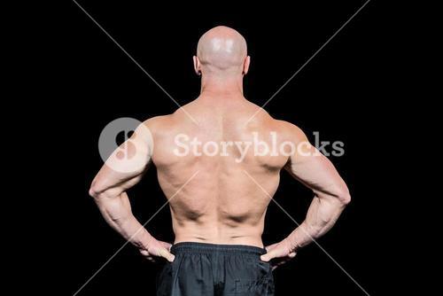 Rear view of confident bald man with hands on hip
