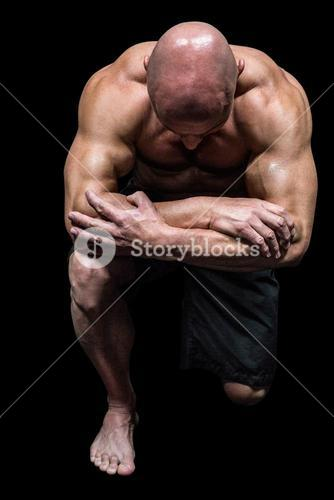 Bodybuilder kneeling down