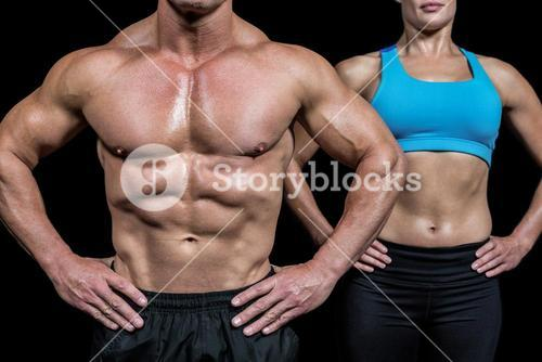 Midsection of man and woman with hands on hip