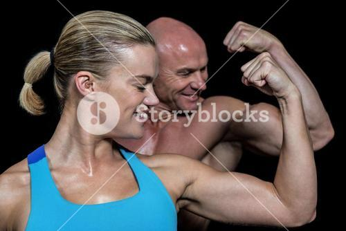 Happy healthy man and woman flexing muscles