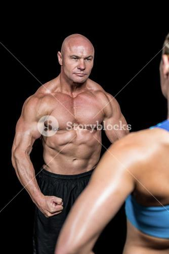 Bodybuilder flexing muscles in front of instructor