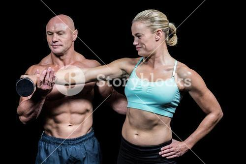 Trainer helping woman for lifting dumbbell