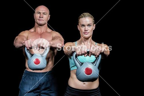 Portrait of muscular man and woman lifting kettlebells