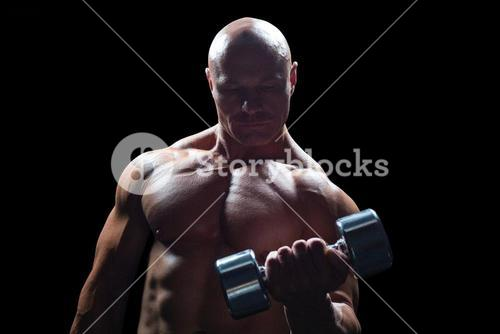 Concentrated bodybuilder lifting dumbbell
