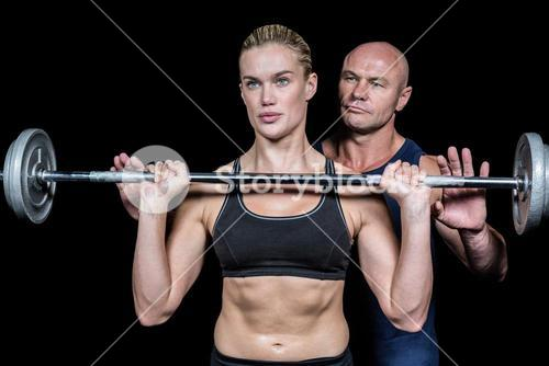 Trainer assisting woman for lifting crossfit