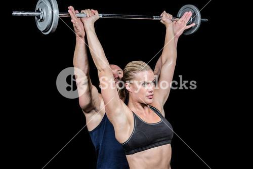Male trainer assisting woman for lifting