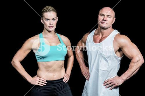 Portrait of confident athlete man and woman with hands on hip