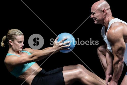 Trainer assisting woman doing crunching exercise